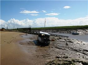 Muddy river bank with a small boat on it. Water can still be seen in the channel to the right.