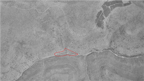 An aerial view of a deep stream valley with a road running left to right and smaller valleys joining it from top and bottom. A red roughly triangular shape is in the center.