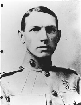 Young man with slicked-down short hair in a circa 1915 U.S. Marine uniform with a very high collar.