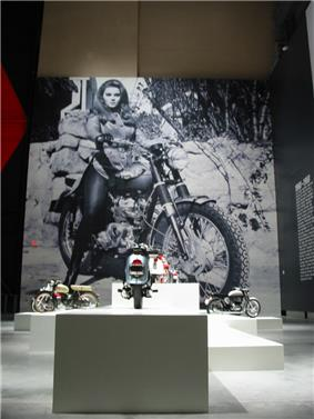 A giant black and white image on the wall of a voluptuous woman with medium-colored hair sitting on a motorcycle.  In the foreground are three motorcycles on pedestals.