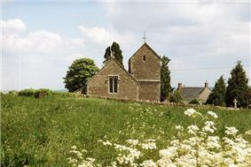 Stone building with tower beyond field and stone wall.