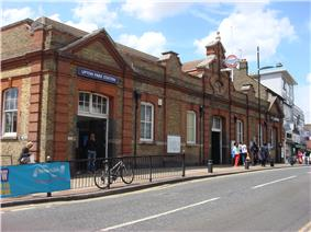 A red-and-brown bricked building with a rectangular, dark blue sign reading