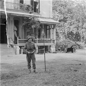 Men standing in front of building next to a small flag pole
