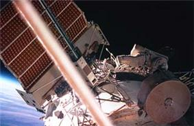 A man dressed in a spacesuit seen crawling along a white, cylindrical space station module. A large solar array can be seen projecting from the top of the module, and various other pieces of apparatus are visible. The Earth's horizon and space are visible behind the solar array.
