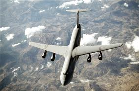 Top view of four-engine jet transport in-flight above mountain range.