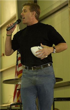 A man wearing a black shirt with blue jeans while clutching a football.
