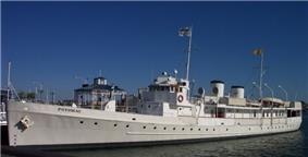 Photograph of the Presidential yacht USS Potomac at dock on a sunny, clear day.