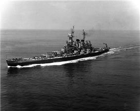 Black-and-white photo of battleship steaming left of screen