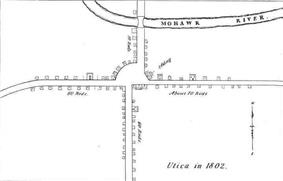 A black-and-white map, depicting buildings and roads in simple, small black outlines. The text