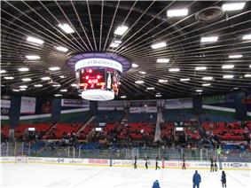 A brightly lit hockey arena, panning upward to show a sloped ceiling and a large, cylindrical television screen.