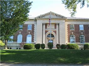 A two-story brick building with pillars, arched windows, and a flagpole in front. A tree is located on the left, and a lawn is in the foreground.