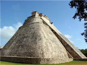 Stone pyramid with smooth surfaces and rounded corners. A staircase on one side leads to a structure at the top of the pyramid.