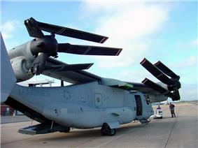 A V-22 with its wing rotated 90 degrees so it runs the length of the fuselage