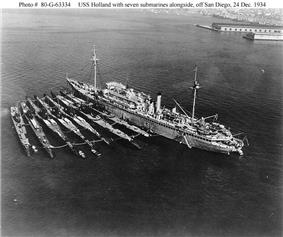 Seven V-boats (from left to right: Cachalot, Dolphin, Barracuda, Bass, Bonita, Nautilus, Narwhal, with submarine tender Holland