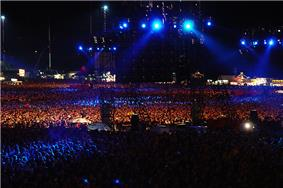 Darkened stadium concert, with blue lights