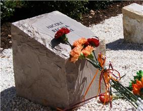 A photo of one of the commemorative stones at the memorial with flowers laid on top of it.