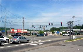 A signalized five-way intersection of three highways in an area composed of several commercial establishments.