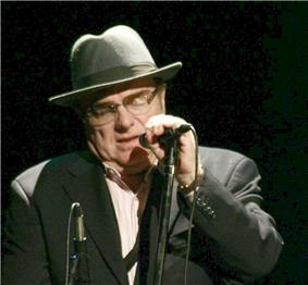 Man wearing a grey hat and grey jacket and glasses holding a microphone near his face.