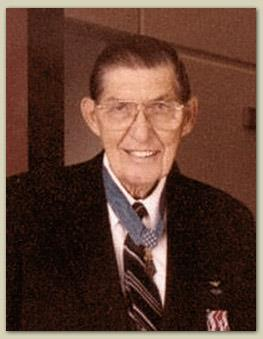 Color photo of Barfoot wearing his Medal of Honor and a blue suit. He is facing the camera and smiling.