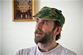 Vikernes looking aside, wearing a camouflage hat