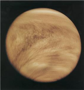 Light brown clouds wrap around a planet, as seen from space.