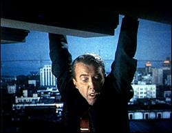 A man, seen from mid-chest up, hangs by his hands from the edge of an apparently tall structure, gazing down in fear. He is wearing a dark suit and an orange tie with a clip. In the distance behind him is a cityscape at night or in the early morning. There is a bluish cast to the background.