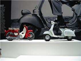A 1960s Italian scooter and a 1960s single cylinder Japanese motorcycle in front of a giant image on the wall of the front wheel and fender of a 1960s Italian scooter.