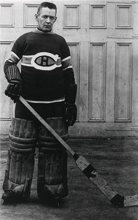 An ice hockey Goaltender stands, also wearing a Canadians jersey, small leg pads and old style gloves, he also is without a mask, while posing for the photo but it was also the style of the time.
