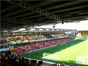 A two-tiered seating area featuring red, yellow and black seats, running along the length of a football pitch.