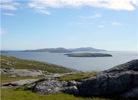 A rocky moorland in the foreground and low, dark islands against a blue sky in the background.