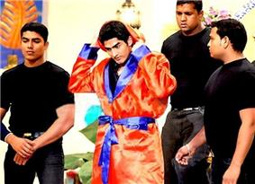 Four men standing. Middle of them is a young Indian male who wears a shiny orange dressing gown with blue border. His hands are behind his head. The other three men are all dressed in black and appear to be waiting around the man.