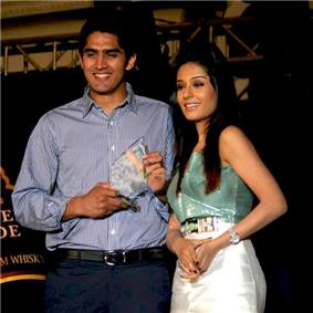 An young Indian male and a female standing side-by-side. The man is on the right and wears a blue-grey shirt and navy-blue trousers. He is smiling looking down to the right of the camera and holds a glass, triangular shaped trophy in his hands.  The female also looks towards the bottom right and wears a shiny dress whose top portion is light green in color and the skirt area being silvery. Her long black hair falls on her shoulders.