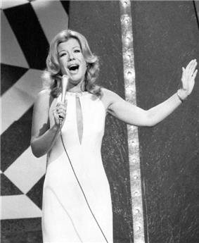 A woman, wearing a dress, holding a microphone.
