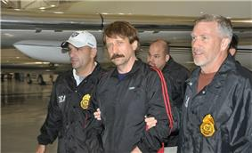 A mustached man, looking at the camera, in a shiny black warmup jacket with red stripes walking between two men wearing black jackets with large gold badge-shaped patches, and white lettering on their sleeves and breasts. It says