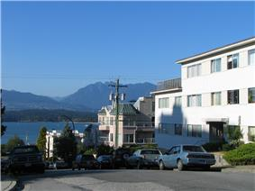 Typical Kitsilano street showing parked automobiles, multi-unit housing, mountains in background.