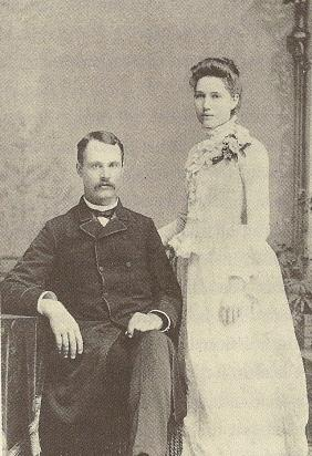 A black-and-white photograph of a couple. On the left is a seated man with a moustache weraing a dark suit. Standing on the right is a woman in a white dress, body facing left.  Both face the camera.