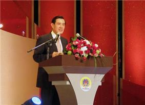Ma Ying-jeou stands behind a podium decked with flowers