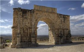 View of a triumphal arch which has two inset columns on each side, in between which are niches, and with a long tablet across the top on which an inscription is written