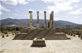 View of the dais of a temple, with an altar standing on a square below and a series of reconstructed columns standing at the head of a set of steps leading up to the top of the dais