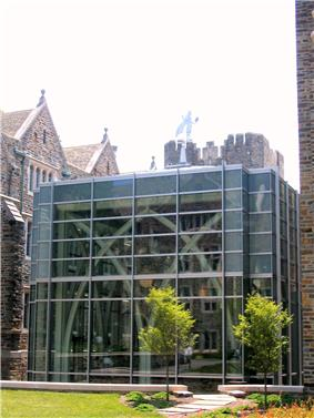 A glass building with a metal blue devil on top and arched details in the interior