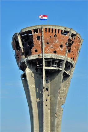 A severely damaged brick and concrete tower, pierced with numerous shell holes