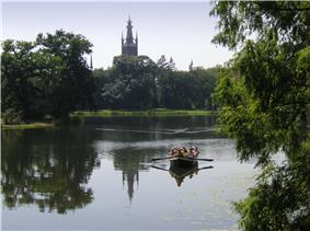 A small row boat navigates a wide river, while a forest stands in the background, hiding a large tower.