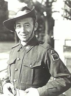 Black-and-white photo of a smiling, clean-shaven man wearing combat fatigues and a slouch hat. He is standing hands on hips with his hands gripping his light-coloured belt.