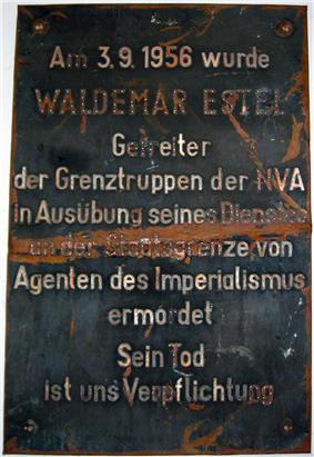 Damaged metal plaque reading