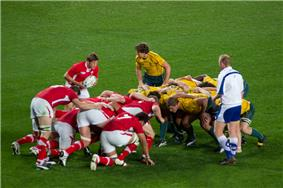 Two packs of players crouched before commencing a scrum