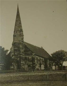Black and white photograph of the church of St John, the steeple prominent against the sky