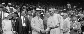 Two men stand in front of a crowd shaking hands. The man on the left of the photo is wearing a tan suit and hat and the man on the right is wearing a light-colored pinstriped baseball uniform.