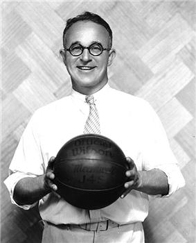 A man holding a basketball. He is wearing a white shirt and tie.