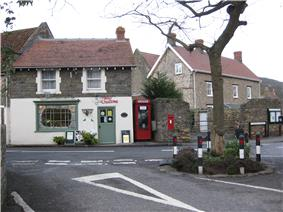 The markings on a road junction around a tree are visible in the foreground, in front of a small shop with Christmas decorations in the window. A red K8 model telephone box and a red post box built into a wall are to the left.