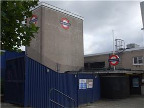 A grey building with a sign on it depicting a blue rectangle superimposed on a white circle superimposed on a red circle